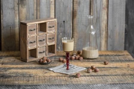 amaretto: Cream liqueur in glass and bottle with hazelnut on wooden backgr Stock Photo