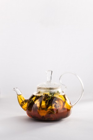 Winter tea with cinnamon, lemon, honey in a teapot isolated on white background.