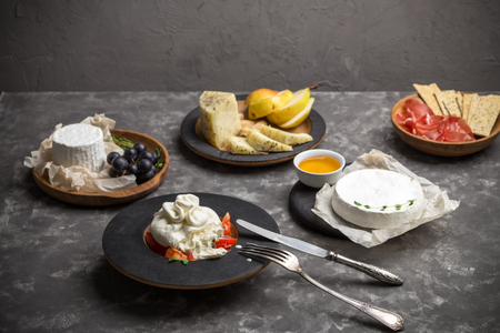 Meat and cheese antipasti snack with Prosciutto ham, Parmesan, burrata, brie and fruits on dark background Stock Photo