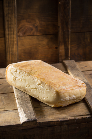 Piece of taleggio cheese on wooden board on dark background. Studio shot