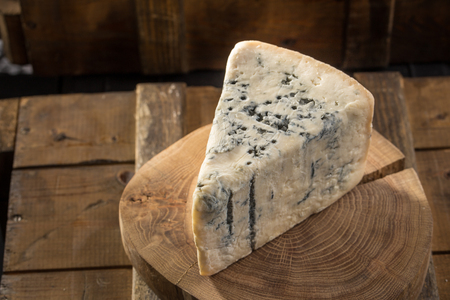 Slice of blue cheese on wooden board on dark background. Studio shot