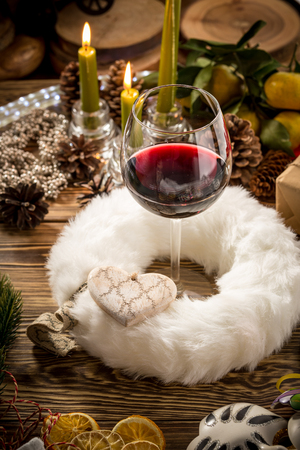 Glass of red wine on wooden table on christmas decorated background. Studio shot