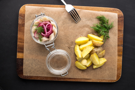 Salted herring with onion and boiled potatoes on wooden board on black background. Studio shot
