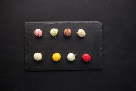 Colorful scoops of ice cream with different flavors on stone board on black background top view