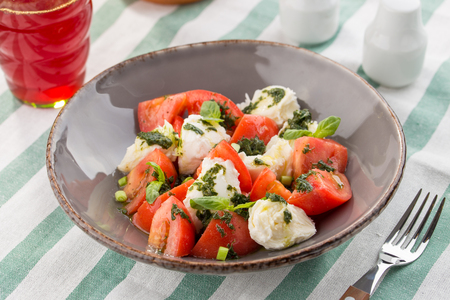 Caprese salad with mozzarella, tomato, basil and balsamic vinegar served on the table studio shot