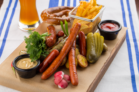 grilled sausages, served with beer, pretzels, pickles and mustard on the side for Octoberfest studio shot