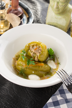 Homemade Meat and Rice Stuffed Bell Peppers with broth served for lunch on the table side view