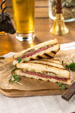 Pastrami sandwich on grilled bread with pickles and mustard on wooden table side view Stock Photo