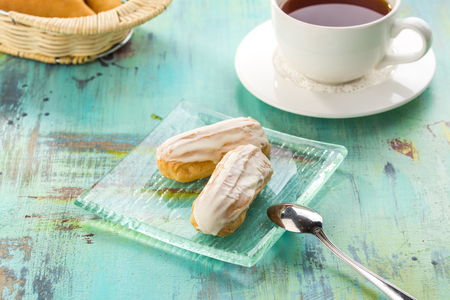 Homemade eclair dessert with vanilla and cup of tea on blue wooden table side view