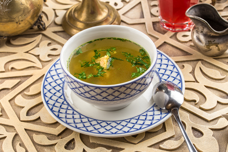 Bowl of fish soup on oriental table background side view Фото со стока