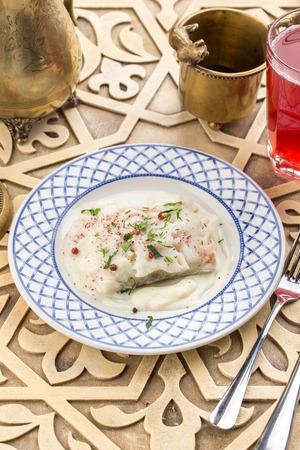 Filete de pescado blanco al horno con salsa blanca en la vista lateral de la mesa oriental