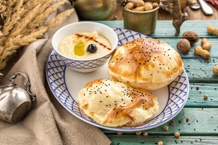 Empanada recién horneada rellena con pasta de queso en la vista lateral de la mesa de madera azul