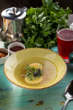 Dietary chicken soup with egg and berry drink on blue wooden table side view