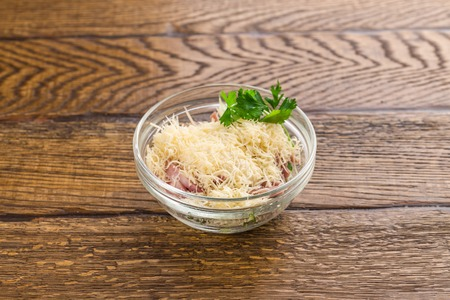 layered vegetable salad with ham isolated on dark wooden background side view