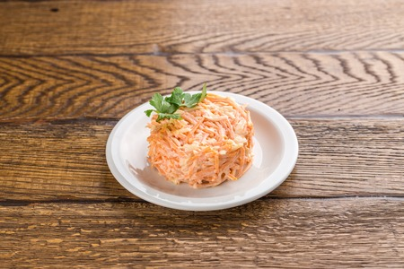 Salad with grated carrot and sour cream isolated on wooden background side view