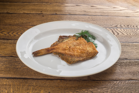 Fried fish flounder on white plate isolated on wooden background side view