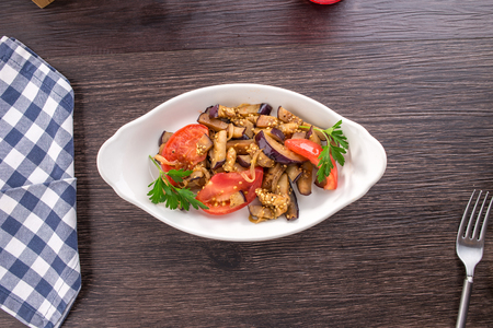 Vegetable salad with fried eggplants and tomatoes on wooden table side view