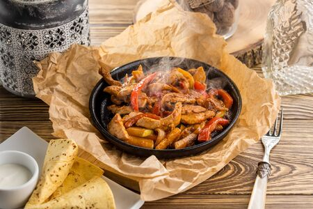 original fajita sizzling smoking hot served on iron plate on wooden table side view