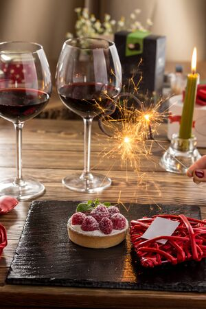 Raspberry tartlets with icing sugar, two glasses of red wine and sparkler on valentine's romantic background