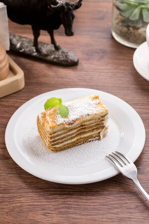 Slice of layered honey cake with mint leaves on wooden table side view Stock fotó