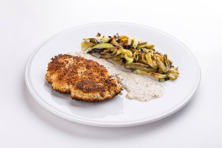 pork schnitzel with fried potatoes and mushrooms and white sauce isolated on white background side view Banque d'images - 127348477