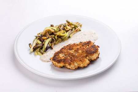 pork schnitzel with fried potatoes and mushrooms and white sauce isolated on white background side view Banque d'images - 127348490