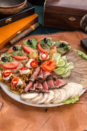 Different appetizer and smoked meat on the plate on old map background side view 免版税图像