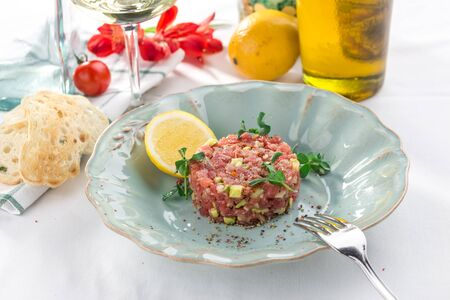 Steak Tartare with bread toasts, lemon and cucumber on white table side view