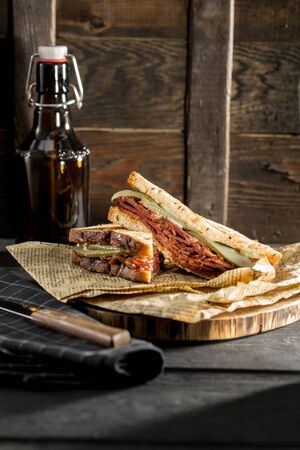 New York sandwich with pastrami, sauce 1000 islands and sauerkraut and beer bottle on wooden background side view 免版税图像