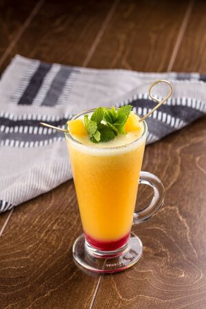 Winter hot drink from oranges and berries in tall glass on wooden table side view