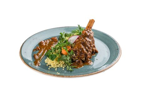 Braised lamb shanks with couscous on blue plate isolated on white background side view Stock Photo