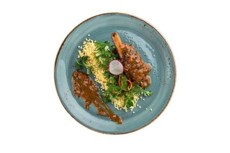 Braised lamb shanks with couscous on blue plate isolated on white background top view