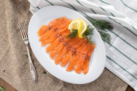 slices of smoked salmon on white plate on tablecloth top view