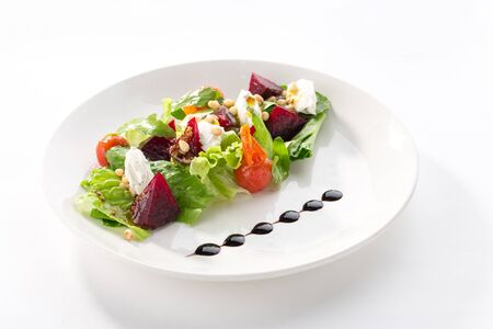 Salad with roasted beetroot, tomato, soft goat cheese isolated on white background side view