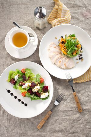 lunch set beetroot cheese salad and roasted turkey fillet with pumpkin and cup of green tea on the table top view Stok Fotoğraf
