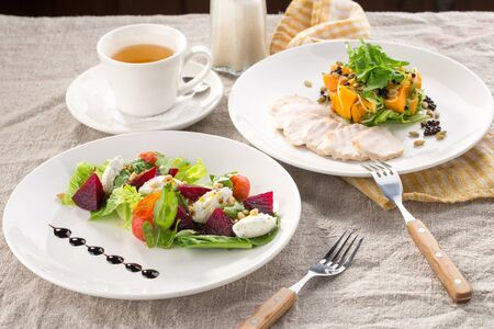 lunch set beetroot cheese salad and roasted turkey fillet with pumpkin and cup of green tea on the table side view
