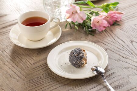 Homemade vegan Raw Energy Balls with honey, poppy seeds and coconut and cup of tea on wooden table side view