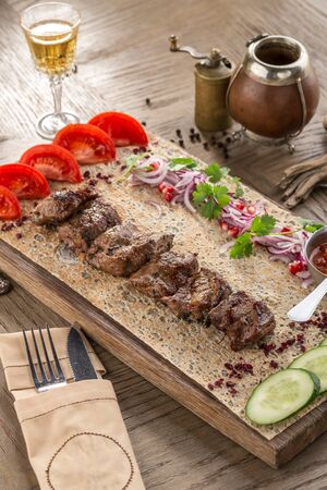 grilled lamb fillet with fresh cucumber, tomato on wooden cutting board on wooden table side view Zdjęcie Seryjne