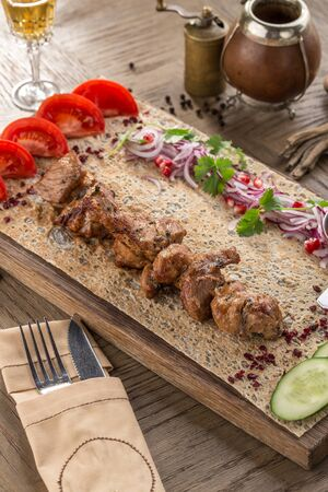 chicken shish kebab on lavash bread with fresh cucumber and tomato on wooden table side view Zdjęcie Seryjne