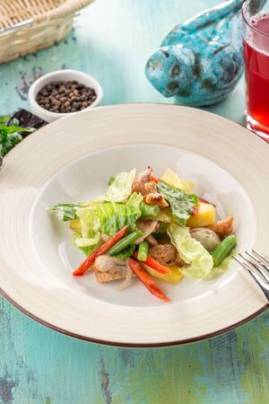 Healthy Grilled Chicken Salad with fresh vegetables and glass of red drink on blue wooden table side view