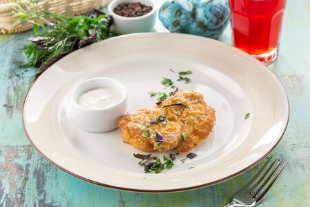 chicken fillet baked with melted cheese and white sauce on blue wooden table side view