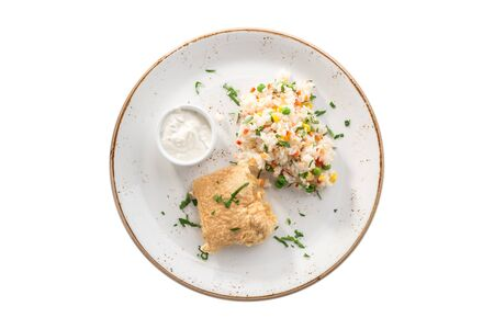 deep fried fish fillet in batter with cooked rice with corn and white sauce isolated on white background top view Stock Photo