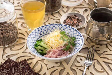 Fresh salad with cucumber, cheese and ham and glass of lemonade on oriental wooden table side view 写真素材