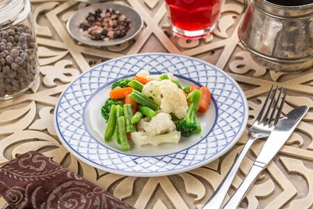 Mixed vegetables cauliflower, broccoli, bean and carrots on white plate and glass of red drink on oriental wooden table side view