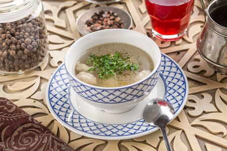 chicken broth with meatballs and parsley in bowl with glass of red drink on oriental wooden table side view