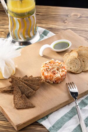 delicious salmon tartar served with rye bread toast and pesto sauce on cutting board on wooden table side view Stock fotó