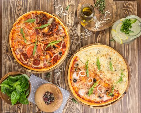 slices of pizza with different toppings and pitcher of lemonde on wooden table top view