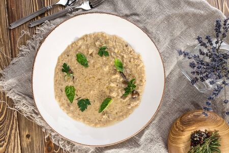 Risotto with porcini mushroom with basil and parsley serving size on wooden table top view