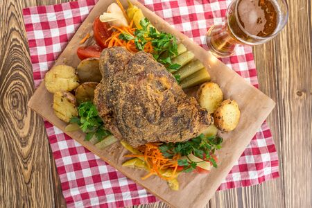 Pork knuckle roast served with potato and pickled vegetables and glass of beer on wooden table top view