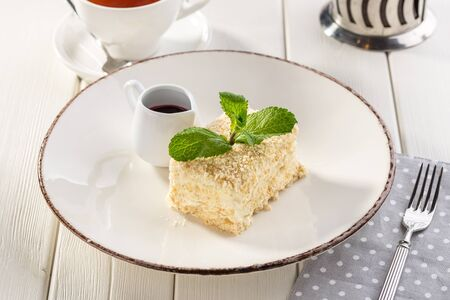 Cake Napoleon puff pastry dessert with cream and cup of black tea on white wooden table side view Stock fotó